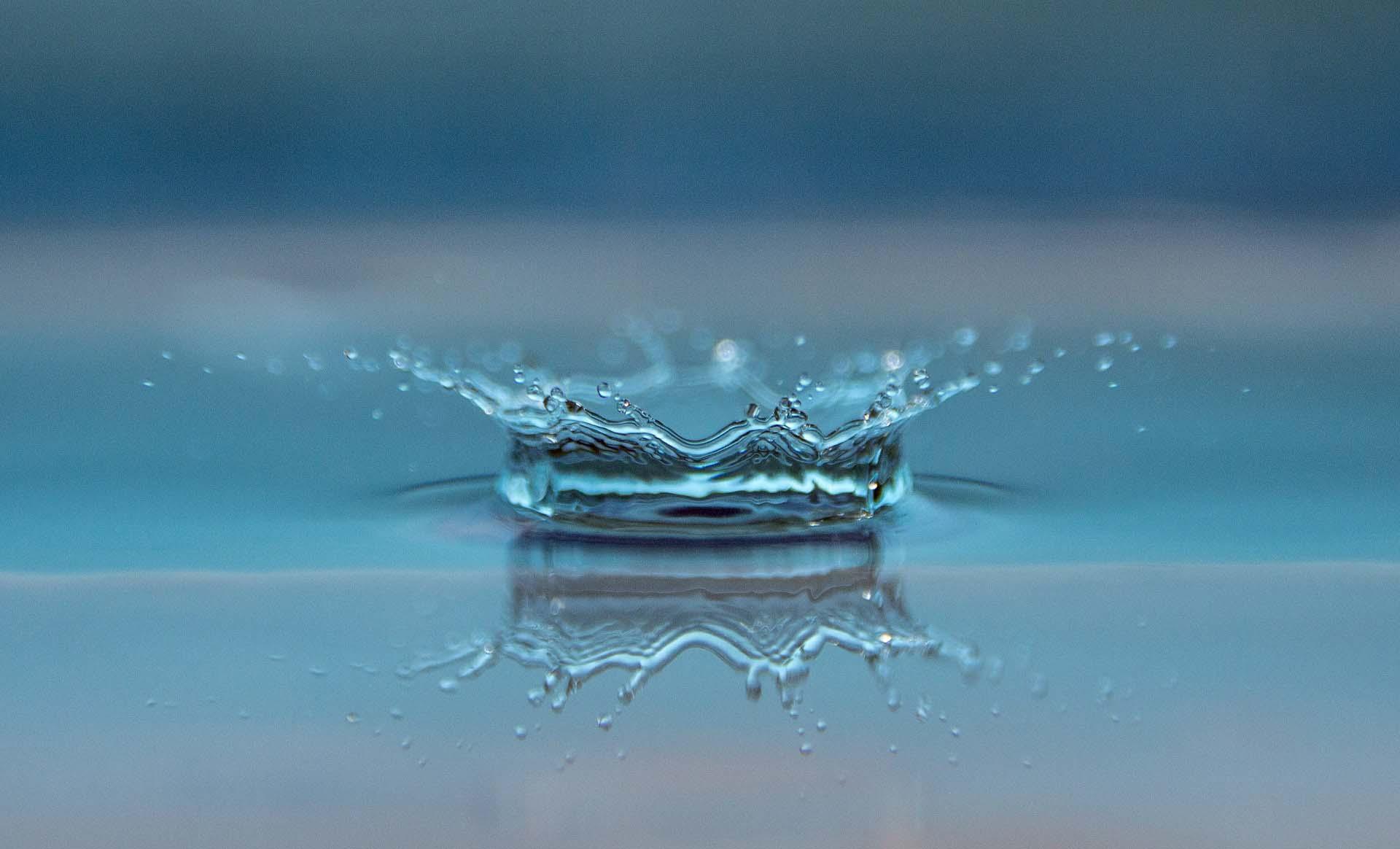 Goutte d'eau tombant sur une surface liquide métaphore du travail sur Soi